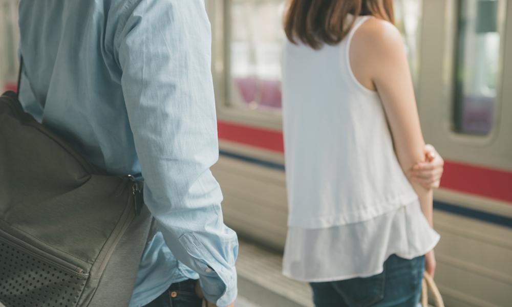 駅のホームで女性の背後に立つ痴漢