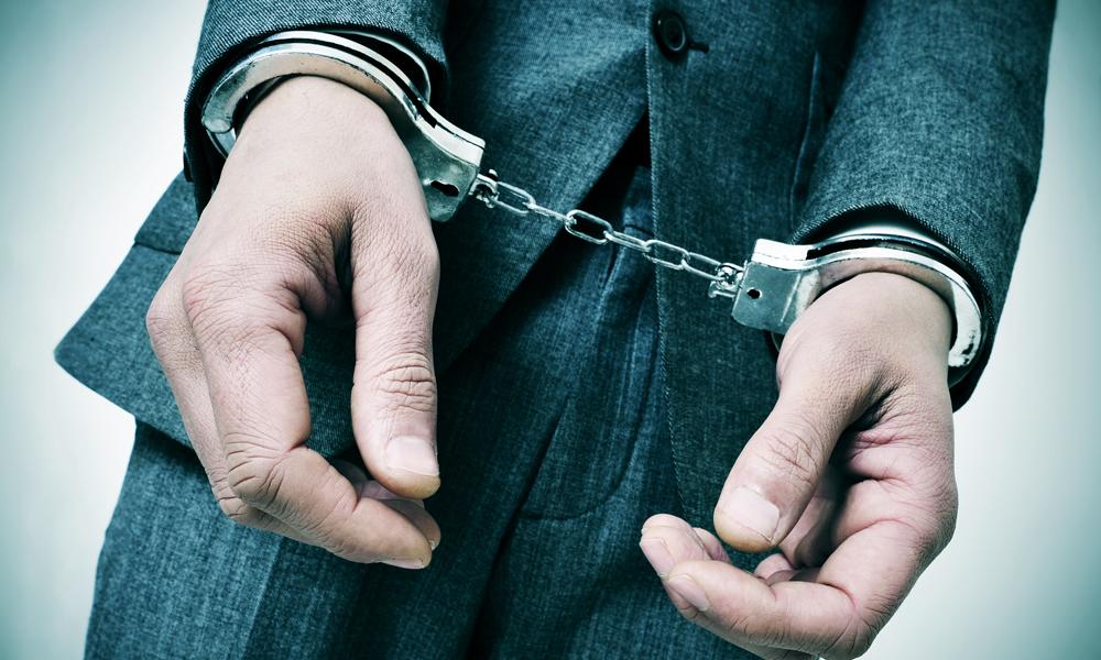 手錠をかけられているスーツの男性